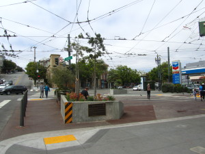 "Jane Warner Plaza - mayo de 2015.  Where are the tables and chairs in this deserted area?  (I see yet another ""straight"" couple in this picture coming into The Castro...ugh.  Are they coming to get drunk like all the other ""straight"" couples that seem desperate to come over here?)."